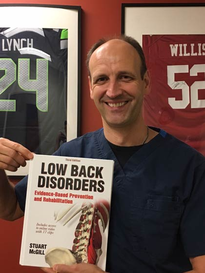 Dr. Kai Tiltmann holding Low Back Disorders by Stuart McGill