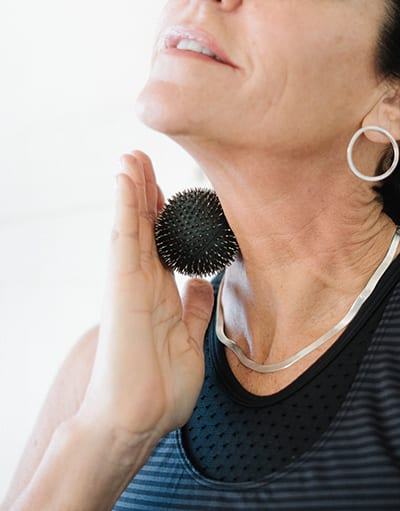 Aku Ball being applied to the neck for pain relief and relaxation